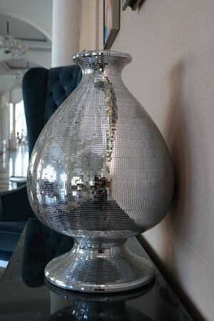 Vase decorated with mosaic of mirror glasses on the table. The glued the mirror vase with some reflection