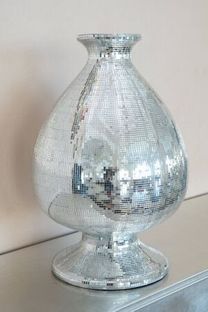 Vase decorated with mosaic of mirror glasses on the table. The glued the mirror vase with some reflection Archivio Fotografico