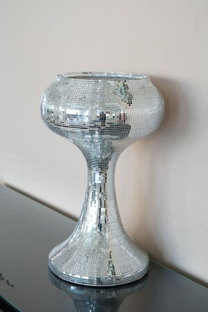 Vase decorated with mosaic of mirror glasses on the table. The glued the mirror vase with some reflection Stock fotó