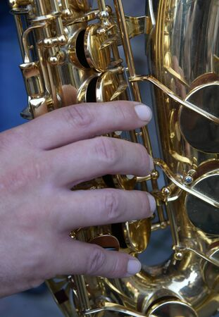 Musical instrument saxophone close-up. Hands on a musical instrument. A musical instrument used by a rock band