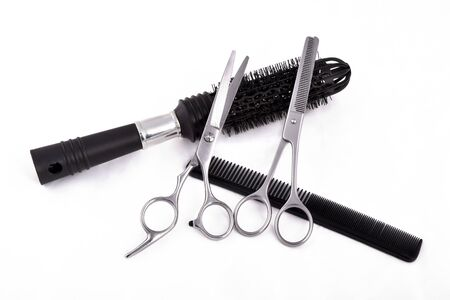 Scissors, brush and comb on white background