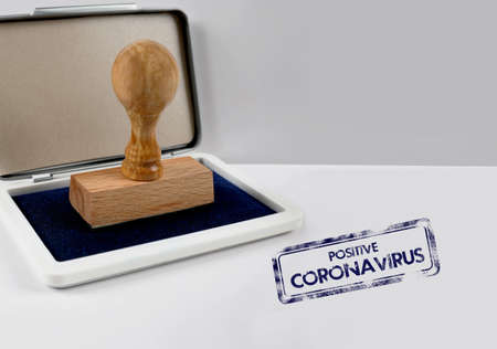 Wooden stamp on a desk POSITIVE CORONAVIRUS