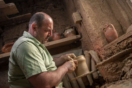 Male potter makes a pot on the pottery wheel. Terracotta pottery guy on spinning wheel. Men making ideas about pottery with a center of land Stock fotó