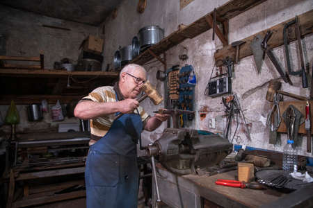 An older man working with sheet metal in his workshop. A worker works carefully with sheet metal