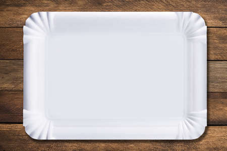 Disposable paper plate on a wooden background. Empty white cardboard plate