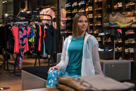 Skopje, Northern Macedonia - March 12, 2021: Asix store in Skopje, Northern Macedonia. Girl photo model dressed in sportswear and sneakers ASICS GEL, sitting and posing in a shop for sports equipment Sajtókép