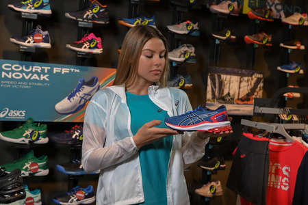Skopje, Northern Macedonia - March 12, 2021: Asix store in Skopje, Northern Macedonia. Girl photo model wearing tracksuits and sneakers ASICS GEL, standing in her arms holding a new model of sneakers
