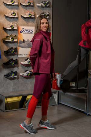 Skopje, Northern Macedonia - March 12, 2021: Asix store in Skopje, Northern Macedonia. Girl photo model wearing a set of dark red tracksuits and sneakers ASICS GEL, standing posing in a sports shop Sajtókép