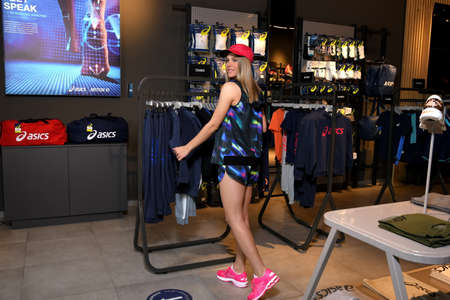 Skopje, Northern Macedonia - March 12, 2021: Asics store in Skopje, Northern Macedonia. Girl photo model wearing sports panties, T-shirt, hat and sneakers ASICS GEL, standing posing in a sports shop