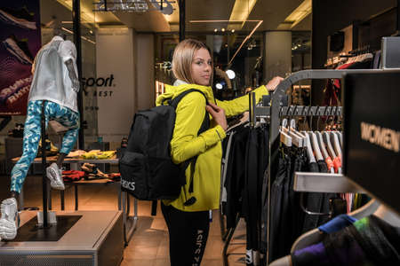 Skopje, North Macedonia - March 12, 2021: Asics store in Skopje, North Macedonia. Girl photo model wearing sports tracksuits and sneakers ASICS GEL, carrying a sports backpack on her shoulder Sajtókép