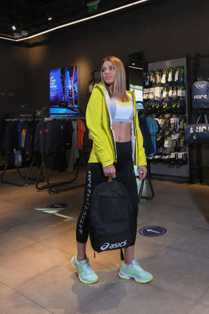 Skopje, North Macedonia - March 12, 2021: Asics store in Skopje, North Macedonia. Girl model wearing sports tracksuits and sneakers ASICS GEL, holding a sports backpack