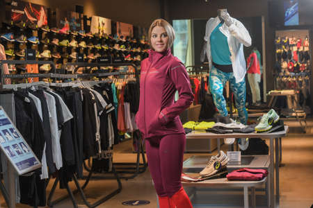 Skopje, Northern Macedonia - March 12, 2021: Asics store in Skopje, Northern Macedonia. Girl photo model wearing a set of dark red tracksuits and sneakers ASICS GEL, standing posing in a sports shop Sajtókép