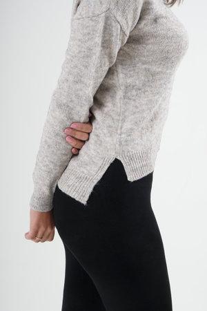 Girl in black leggings and light gray blouse