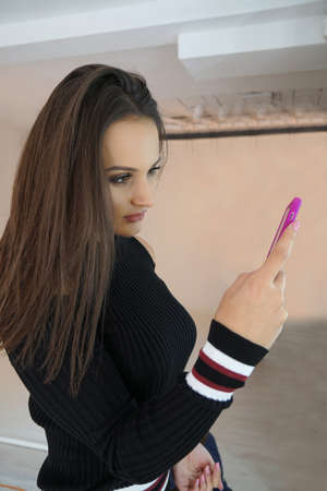 Portrait of an attractive young serious girl  woman using mobile phone. Portrait of a smiling casual woman holding smartphone