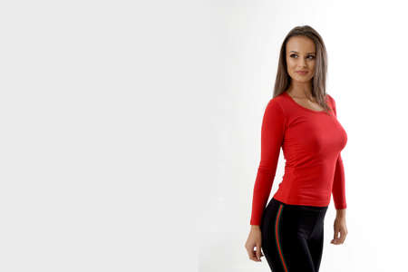 Portrait of an emotionally beautiful woman laughing while looking to the side. Beauty face portrait. Beautiful model girl with perfect fresh clean skin. Girl with red blouse and black tracksuits