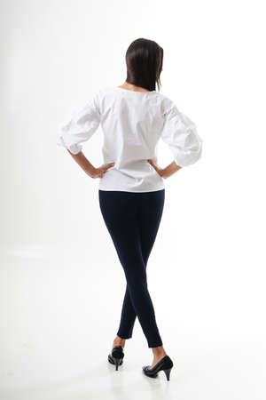 Portrait of woman standing with her back turned, wearing white shirt, black tracksuits with high heels, isolated on white backround. Very attractive woman with unusual and long hair. A girl with beautiful hair turned her back to the audience on a white background. Stock fotó