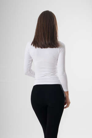 Portrait of woman standing with her back turned, wearing white blouse and black tracksuits, isolated on white backround. Very attractive woman with unusual and long hair. A girl with beautiful hair turned her back to the audience on a white background. Stock fotó