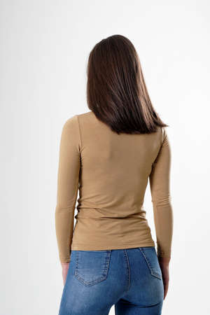 Portrait of woman standing with her back turned, wearing light brown blouse and blue jeans, isolated on white backround. Very attractive woman with unusual and long hair. A girl with beautiful hair turned her back to the audience on a white background. Stock fotó