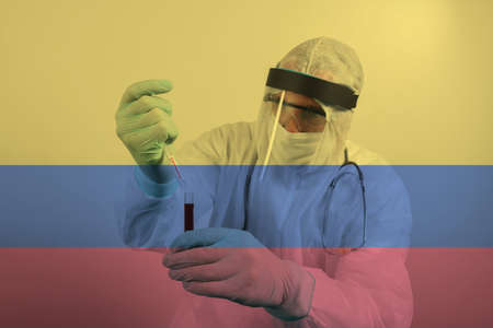 Doctor wearing respiratory mask and holding the Coronavirus Covid-19 blood sample. Scientists test for Covid-19 or Corona virus By using science tubes to research and treat illness in a lab or hospital. Transparent flag of Colombia over the photo Stock fotó