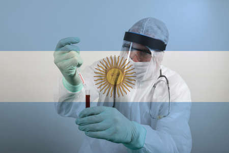 Doctor wearing respiratory mask and holding the Coronavirus Covid-19 blood sample. Scientists test for Covid-19 or Corona virus By using science tubes to research and treat illness in a lab or hospital. Transparent flag of Argentina over the photo