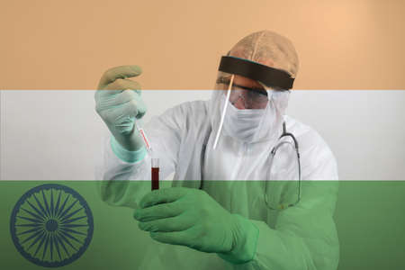 Doctor wearing respiratory mask and holding the Coronavirus Covid-19 blood sample. Scientists test for Covid-19 or Corona virus By using science tubes to research and treat illness in a lab or hospital. Transparent flag of India over the photo Stock fotó