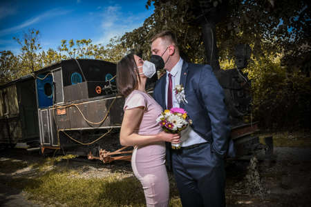 Wedding couples in medical masks poses in park. Newlyweds during Coronavirus pandemic in facial masks. Groom and bride kissing each other in protective medical masks on face in