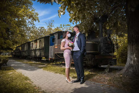 Wedding couples in medical masks poses in park. Newlyweds during Coronavirus pandemic in facial masks