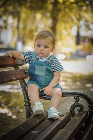 Kid's concept, emotions.Cute little boy staying in park and pensively looking at camera