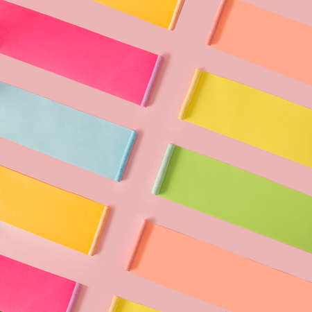 Creative patern of pastel colored chalk with colorful long shadow on pink background. Creative flat lay patern.