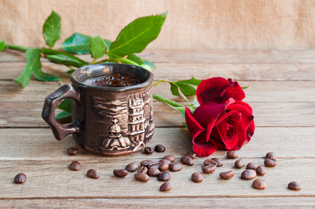 Cup of coffee and red roses on a wooden table