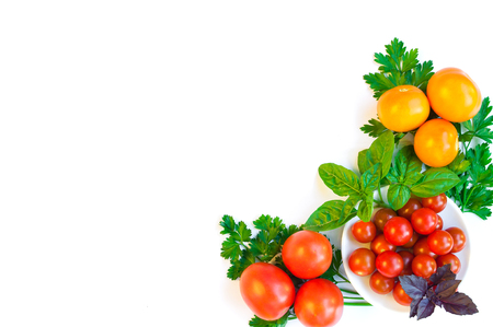 Cherry tomatoes, yellow and red tomatoes and greens on a plate isolated on white