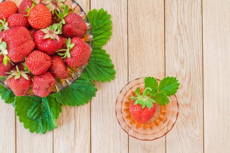 Fresh ripe strawberries in a plate on a wooden background. Top view. Stock Photo