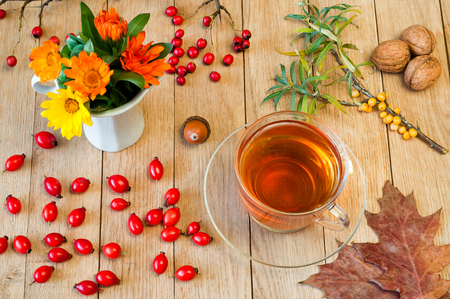 concep: Black herbal tea in a transparent cup on a wooden table. Autumn concep