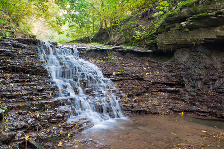 Beautiful waterfall on a mountain stream in the woods Stock Photo
