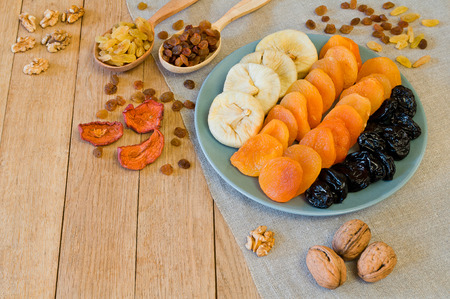 Different dried fruits on a plate on a wooden table
