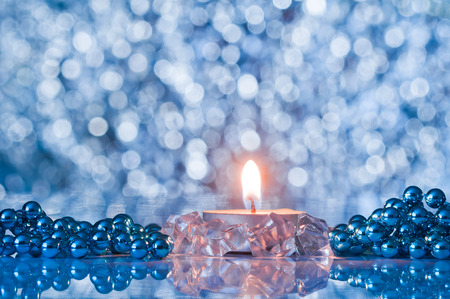 Flame of candle and Christmas decorations on the background bokeh Stock Photo