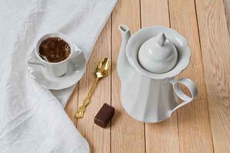A cup of coffee on a plate of white porcelain set on a wooden table
