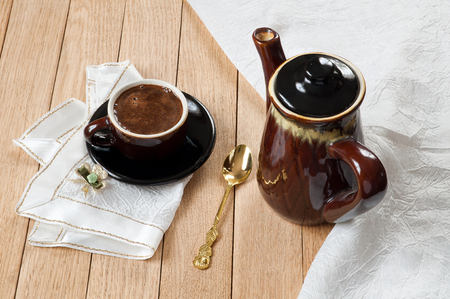 Coffee in a dark porcelain cup on a wooden table Stock Photo