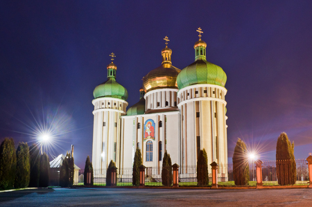 Church in the light of evening lanterns. Holy Protection Church in the city. Dubno, Ukraine Stock Photo