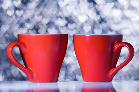 Two red cups on the background bokeh in the shape of hearts