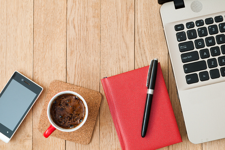 Closeup notepad with a pen, cup of coffee, a smartphone and a laptop on a wooden table. Business concept