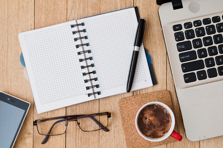 Closeup open notepad with pen, cup of coffee, glasses, a smartphone and a laptop on a wooden table. Business concept