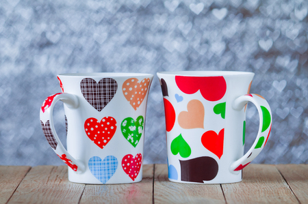 Two cups with hearts on bokeh background in the form of hearts Stock Photo