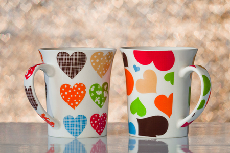 Two cups with hearts on a background of golden bokeh in the shape of hearts Stock Photo