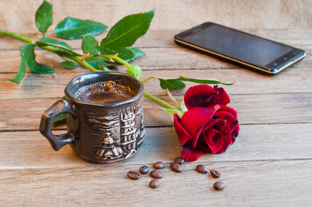 A cup of coffee, a red rose and a smartphone on a wooden table  Stock Photo