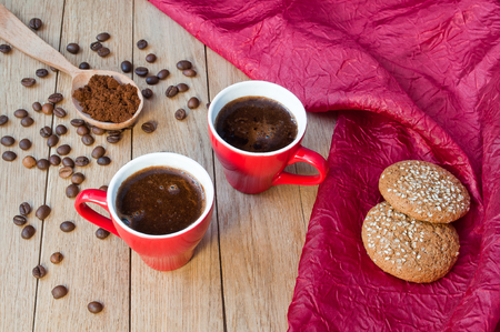 Two red cups of coffee with oatmeal cookies on a wooden table