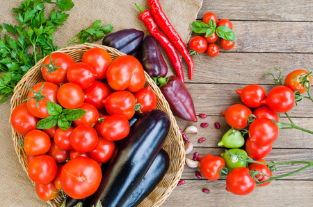 Tomatoes, eggplants in basket and other vegetables on sacking and wooden background Stock Photo