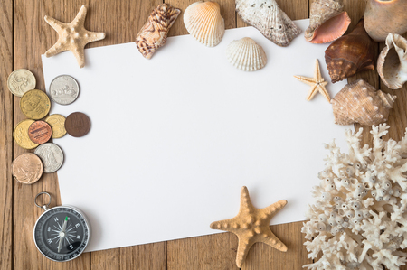 Coins, sea shells, stars and corals on a wooden table. Travel concept.