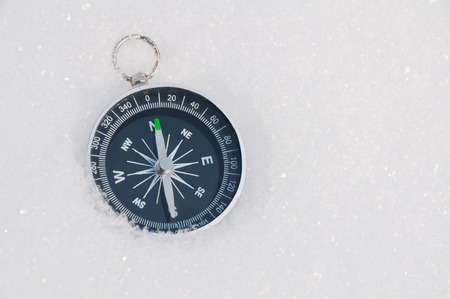 Tourist compass on a background of white snow on a sunny day
