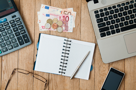 Closeup open notepad with pen, a laptop, a calculator, a smartphone and money on a wooden table. Business concept